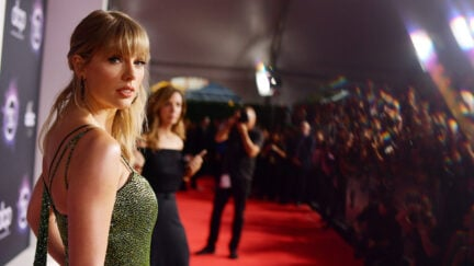 Taylor Swift looks at the camera to the side of a red carpet setup