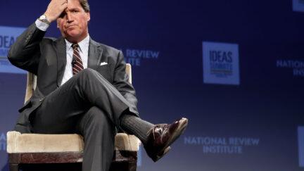 Tucker Carlson sits cross-legged, scratching his head during a talk at a convention