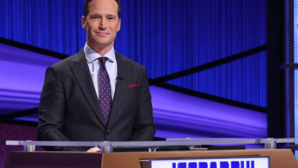 Mike Richards stands at the host podium during an episode of Jeopardy.