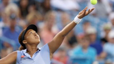 Tennis star Naomi Osaka in mid-serve