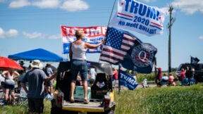 A small crowd gathers outside with a woman stands on the bed of a pickup truck holding a Trump 2020 flag and a Q Anon flag