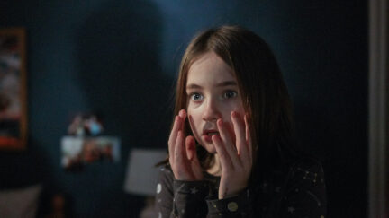 A young girl holds her hands up to her face with a scared expression in a still from Martyrs Lane.