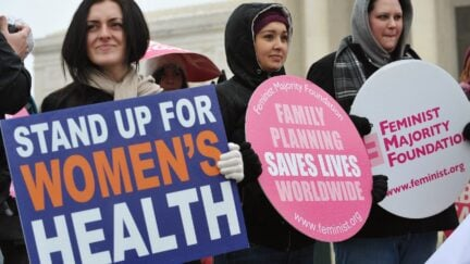 Pro-choice activists hold placards during a rally, one of which reads