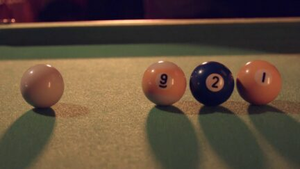 Billiard balls on a pool table, from left to right the white cue ball, 9, 2, and 1.