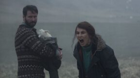 Björn Hlynur Haraldsson holding their adopted lamb-child next to Noomi Rapace, who is shouting. (Image: A24.)