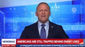 Newsmax host Grant Stinchfield yells on air.