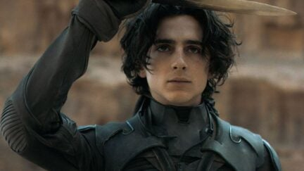 Paul (Timothee Chalamet) holds up a knife above his head in a scene from Dune.