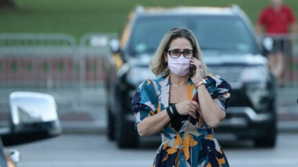 Kyrsten SInema wears a mask and a bright floral dress, talking on a cell phone in a parking lot