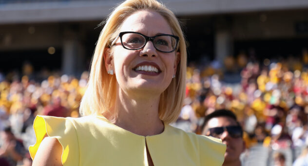 Kyrsten Sinema looks out at a crowd, smiling