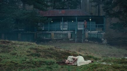 A woman in a white dress lies curled up in a field in the horror movie 'She Will'