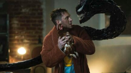 Venom yelling at Eddie while he holds a chicken in Venom: Let There Be Carnage